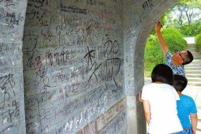 今年6月18日,几名游客正在慈济寺山门的墙上涂写。慈济寺门洞里已被写满留言。
